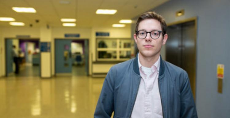 Young man standing in hospital corridor
