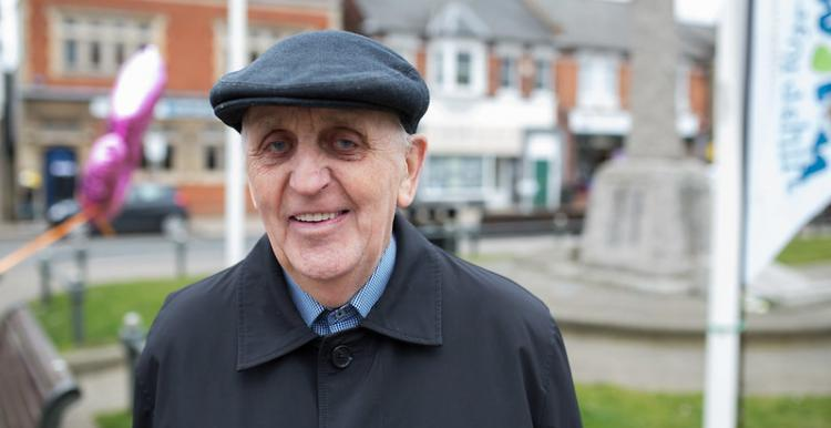 Older man facing front smiling at camera