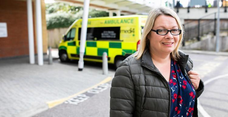 woman posing for camera with ambulance in the background