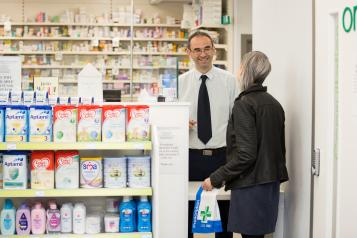 Lady holding collected prescription talking to a pharmacist in the pharmacy
