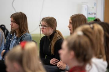 Group of young people sitting listening