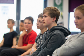 Teenage boy by sitting in a row of teenagers looking towards the front of the room