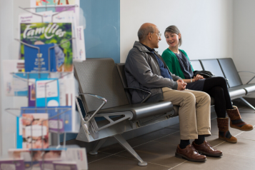 Young woman and older man sitting in hospital waiting seats