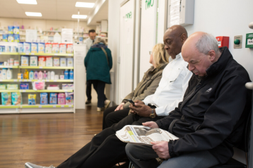 Three people sitting waiting at a pharmacy