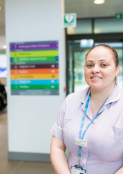 Nurse standing in a hospital with signage behind her