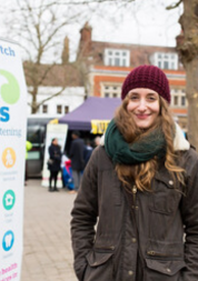 Young lady wearing a hat and coat standing next to a Healthwatch banner